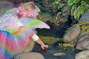 Little girl in fairy costume playing with rock pool
