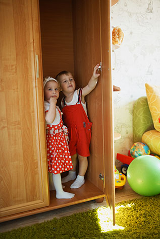 boy and girl playing hide and seek in closet