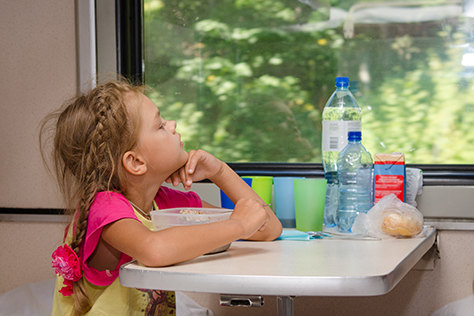 A six-year girl in a train sitting at a table with food on a lower place in the second-class compartment of the car and looks thoughtfully out the window