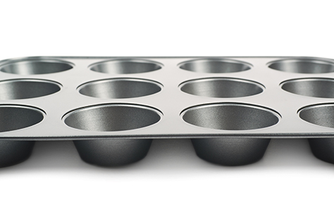 Metal muffin cupcake tray pan isolated over the white background, close-up crop fragment