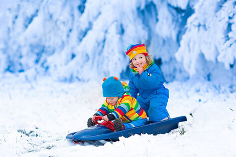 kids playing with sleigh in snow